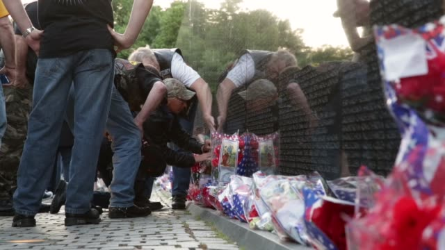 family and friends rub a name of their love one on a piece of paper from the wall of the vietnam veterans memorial prior to the memorial day weekend.... - vietnam veterans memorial video stock e b–roll