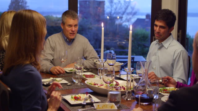 MS Family and friends sitting at dining room table together during dinner