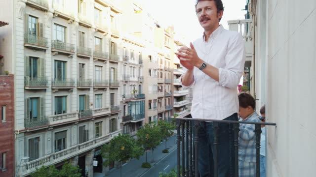 vídeos y material grabado en eventos de stock de familia aplaudiendo al personal médico desde el balcón por covid-19. slo mo. - confinamiento