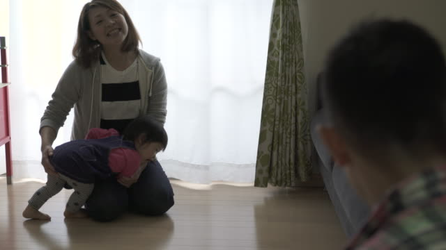 family are playing in the living room together - 床点の映像素材/bロール