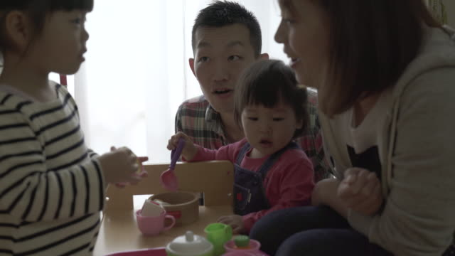 family are playing in the living room together - 住宅購入点の映像素材/bロール