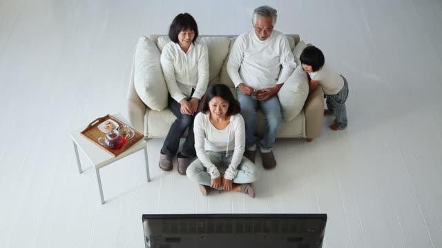 ms family are watching television / fujikawaguchiko, yamanashi, japan - sofa点の映像素材/bロール