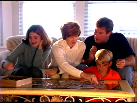 family assembling puzzle - see other clips from this shoot 1335 stock videos and b-roll footage