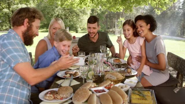 vidéos et rushes de slo mo famille lors d'un pique-nique en regardant une photo de smartphone - picnic