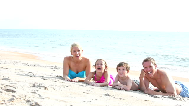 family at beach lying on sand, get up and run away - four in a row stock videos & royalty-free footage