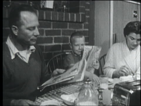 B/W 1958 family at breakfast table / son imitates father reading newspaper + sipping coffee