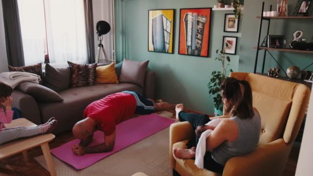 vídeos de stock, filmes e b-roll de família em casa durante a quarentena - homem se exercitando na sala de estar - isolado