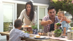 Family At Home Eating Outdoor Meal In Garden Shot On R3D