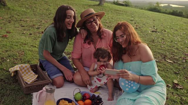 vídeos de stock, filmes e b-roll de família em piquenique ao pôr do sol - família de várias gerações
