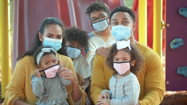 family at playground, wearing face masks during covid-19 - family with four children stock videos & royalty-free footage