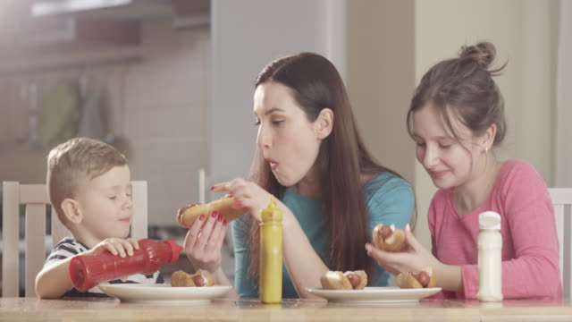 vídeos de stock e filmes b-roll de family at the kitchen table preparing hotdogs and enjoying food having great time shot on red camera - unhealthy eating