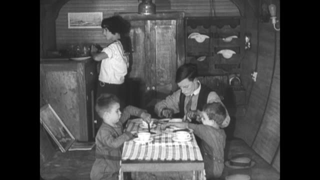 1921 family attempt to eat dinner in the cabin of a moving boat - 1921年点の映像素材/bロール