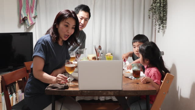famiglia che partecipa a video meeting online e cena insieme a casa - happy hour video stock e b–roll