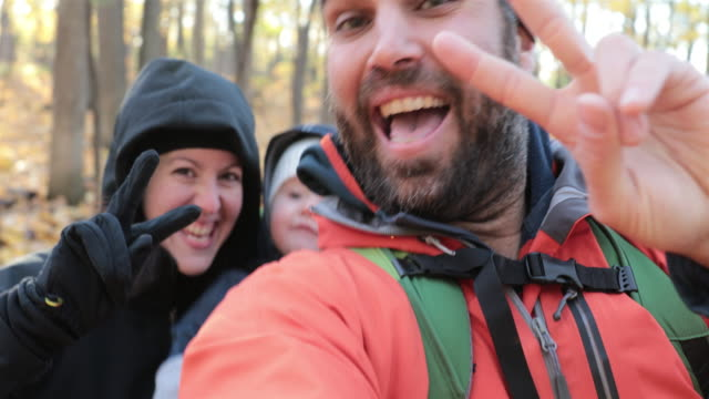 family backpacking hiking with baby in autumn forest - symbol stock videos & royalty-free footage