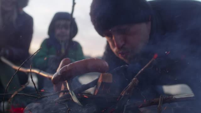 familj bakning middag i brasan. vinter nöje. riverside i staden - vedbrasa bildbanksvideor och videomaterial från bakom kulisserna