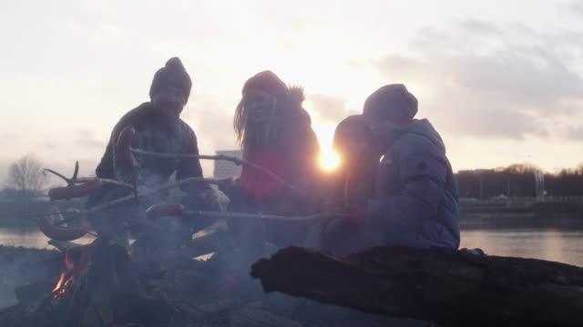 family baking dinner in the bonfire. winter fun. riverside in the city - evening meal stock videos & royalty-free footage