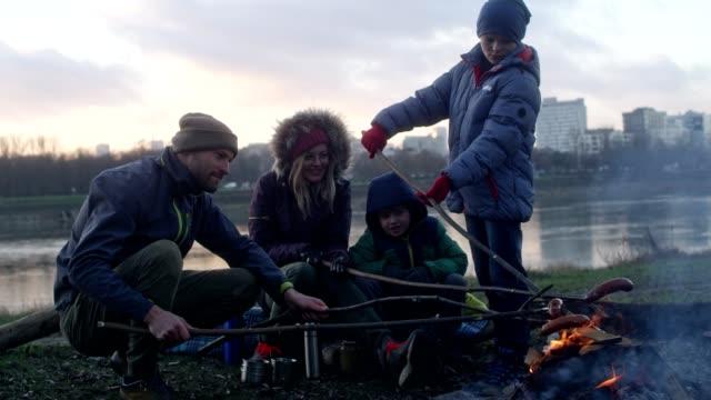 familj bakning korv i brasan. vinternöje. riverside i staden - vedbrasa bildbanksvideor och videomaterial från bakom kulisserna