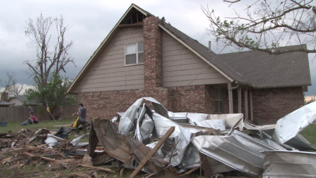 stockvideo's en b-roll-footage met a family begins to clean up the area around their damaged home in the wake of the devastating ef5 tornado in moore oklahoma on may 20th 2013 - 2013