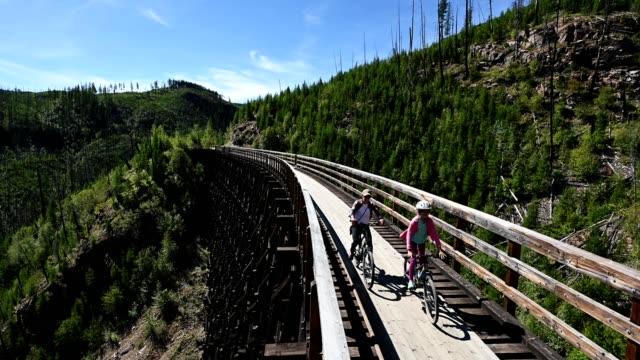 family biking at the myra canyon trestles near kelowna - active lifestyle stock videos & royalty-free footage