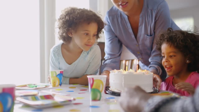 family blowing candles on birthday cake - birthday cake stock videos & royalty-free footage
