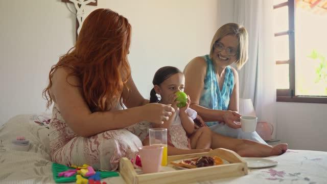 vídeos de stock e filmes b-roll de family breakfast in bed - sentar se