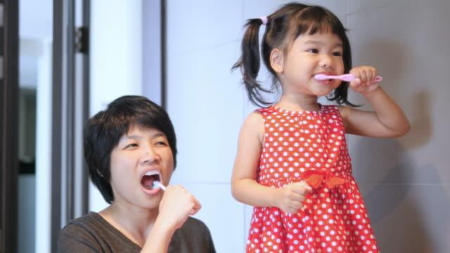 vídeos de stock, filmes e b-roll de dentes de escovadela da família - escovar dentes