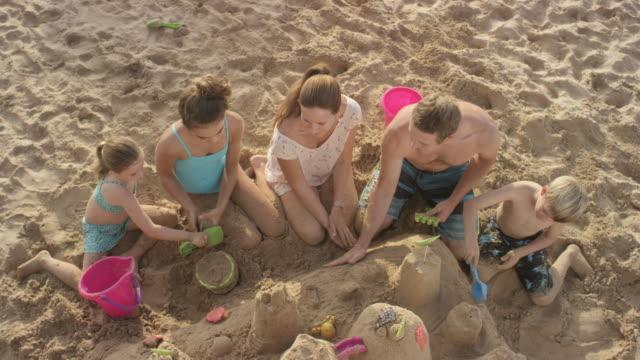 Familj bygga ett sandslott på en tropisk strandsemester till Hawaii