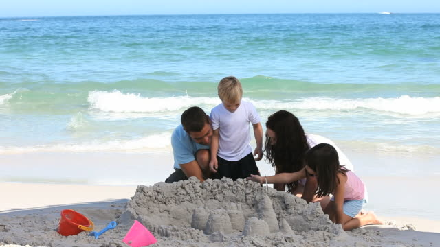 WS Family building sand castle on beach / Cape Town, Western Cape, South Africa
