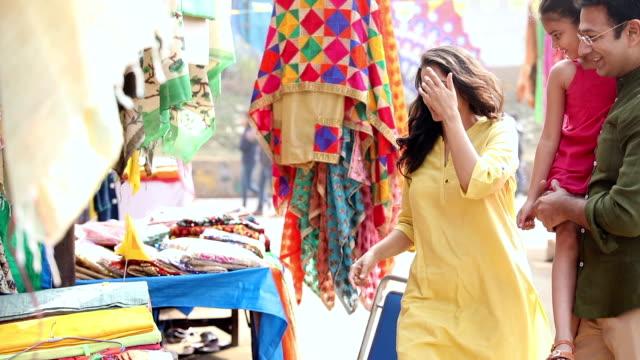 Family buying clothes at Suraj Kund fair, Haryana, India