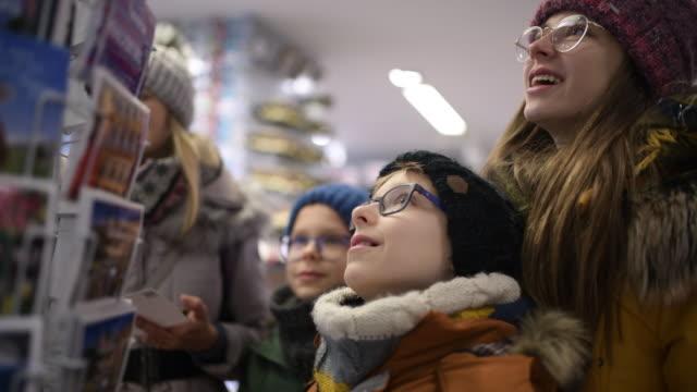 family buying postcards in souvenir shop - souvenir stock videos & royalty-free footage