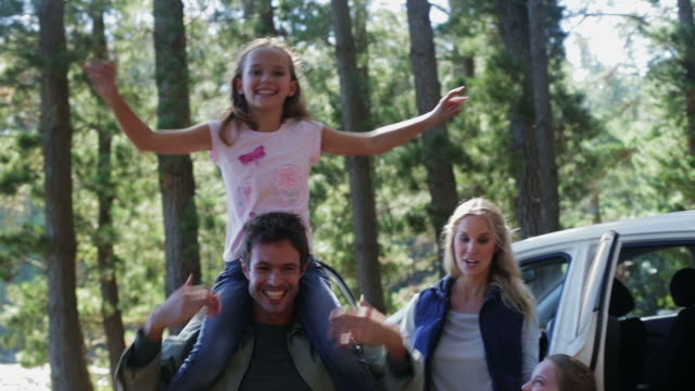 stockvideo's en b-roll-footage met ms of family by car in forest - autoreis