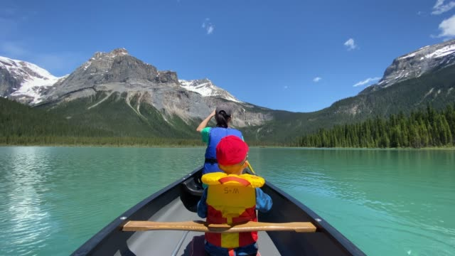 pov family canoeing at emerald lake in summer, yoho national park, british columbia, canada - mountain range stock videos & royalty-free footage