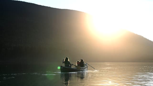 family canoeing on a stunning mountain lake - canada stock videos & royalty-free footage