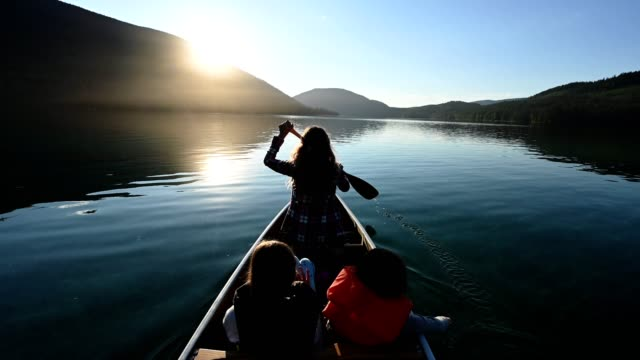 family canoeing on a stunning mountain lake - reportage stock videos & royalty-free footage