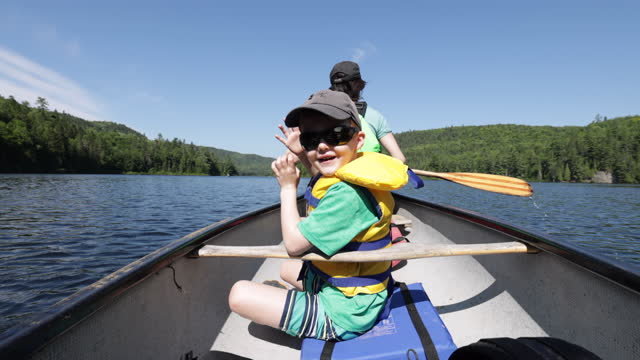pov family canoeing on wapizagonke lake in parc national de la mauricie, quebec, canada in summe - lake stock videos & royalty-free footage