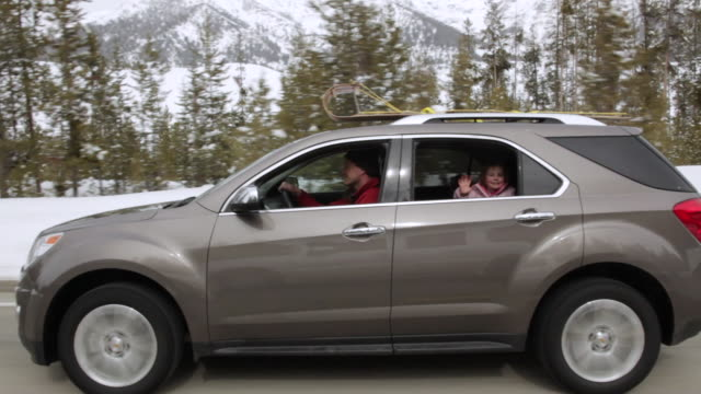 ms pov family car driving at snowy day and little girl waving hand at back window / sun valley, idaho, united states - winken stock-videos und b-roll-filmmaterial