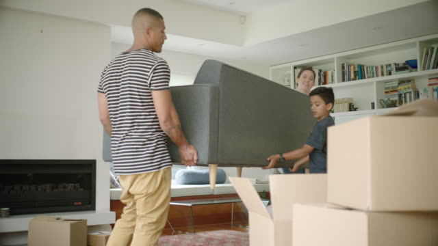 stockvideo's en b-roll-footage met family carry couch into new home - plank meubels