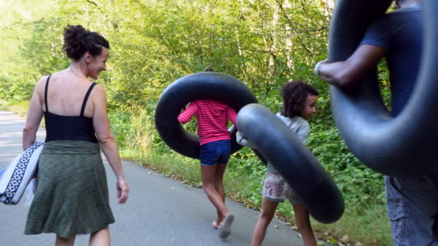 ms family carrying inner tubes down road on the way to river on summer afternoon - reifenschlauch stock-videos und b-roll-filmmaterial
