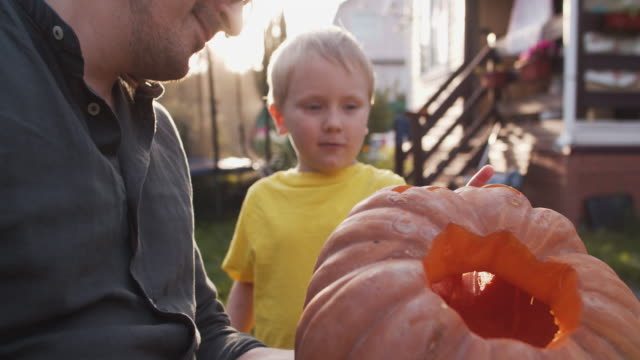 family carving jack o' lantern for halloween outdoors in a sunny evening - carving craft product stock videos & royalty-free footage