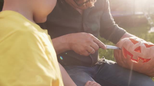 vídeos y material grabado en eventos de stock de talla de la familia jack o' lantern para halloween al aire libre en una noche soleada - decoration
