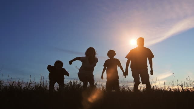 Family celebrate joy at sunset