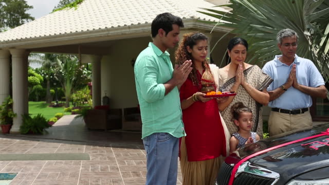 Family celebrating a new car purchase, Delhi, India