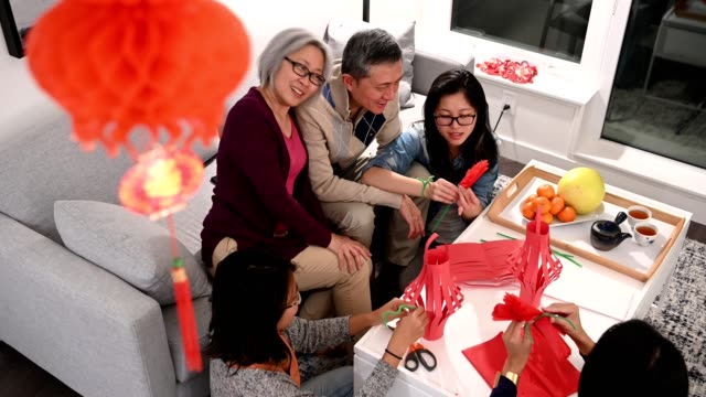 family celebrating chinese new years at home - red stock videos & royalty-free footage