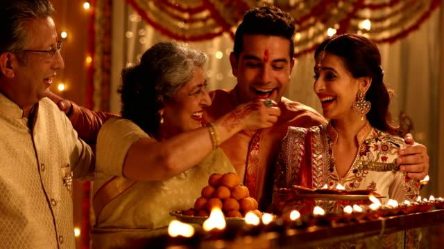 family celebrating diwali festival, delhi, india - sweet food stock videos & royalty-free footage