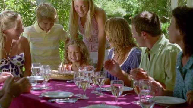 CU, Family celebrating girl's (6-7) birthday in garden, Saint Ferme, Gironde, France