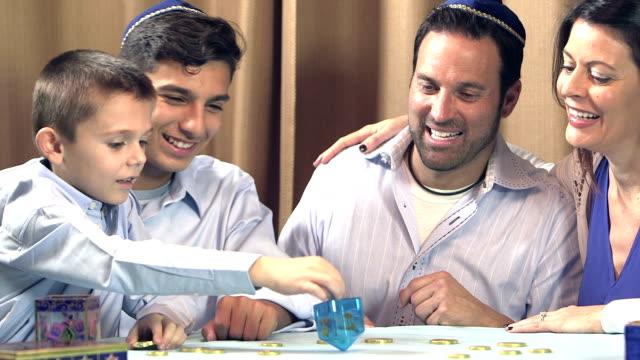 family celebrating hanukkah, playing dreidel - judaism stock videos and b-roll footage