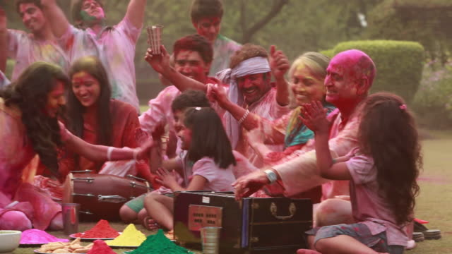 family celebrating holi festival in the lawn  - curly stock videos & royalty-free footage