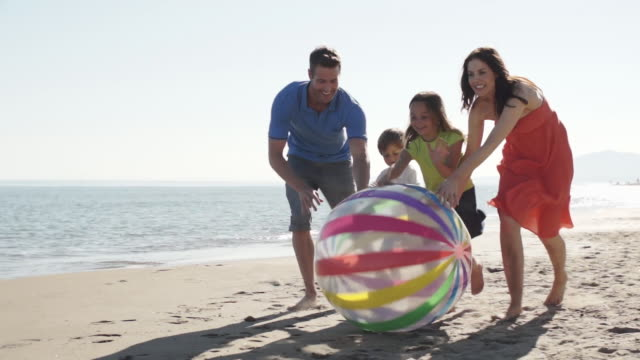 family chasing beach ball along beach - four people stock videos and b-roll footage