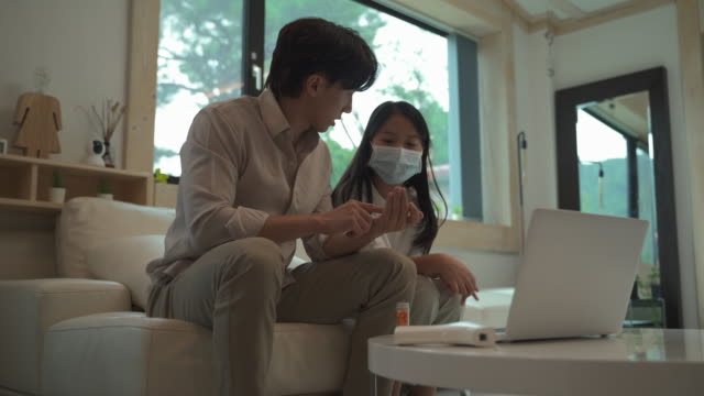 family checking for a fever with thermometer and having telemedicine - 温度計点の映像素材/bロール