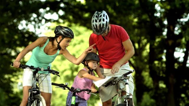 vídeos y material grabado en eventos de stock de hd: verificación de mapa mientras familia ciclismo - dirección